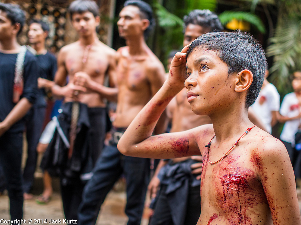 04 NOVEMBER 2014 - YANGON, MYANMAR:  Burmese boys and men pray during a break in flagellation ceremony on Ashura in Yangon. The flagellation shows solidarity with Hussein and his family. Mogul Mosque is the principal Shia mosque in Yangon. Ashura commemorates the death of Hussein ibn Ali, the grandson of the Prophet Muhammed, in the 7th century. Hussein ibn Ali is considered by Shia Muslims to be the third imam and the rightful successor of Muhammed. He was killed at the Battle of Karbala in 610 CE on the 10th day of Muharram, the first month of the Islamic calendar. According to Myanmar government statistics, only about 4% of the population is Muslim. Many Muslims have fled Myanmar in recent years because of violence directed against Burmese Muslims by Buddhist nationalists.    PHOTO BY JACK KURTZ