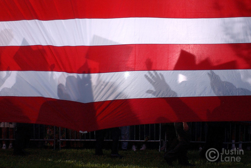 Silouhettes of supporters are seen on an american flag as United States Senator and Democratic Candidate for President John Kerry shakes hands at an early vote rally at the Barnett Park Recreation Center in Orlando, FL Monday, 18 Oct, 2004. Kerry is campaigning in Florida today...EPA/JUSTIN LANE
