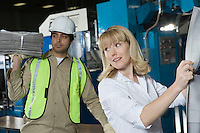 Woman checking newspaper in factory with colleague in background