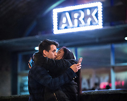 "© Licensed to London News Pictures . 17/12/2016 . Manchester , UK . A couple embrace and kiss whilst operating their mobile phones at Deansgate Locks . Revellers out in Manchester City Centre overnight during "" Mad Friday "" , named for being one of the busiest nights of the year for the emergency services in the UK . Photo credit : Joel Goodman/LNP"