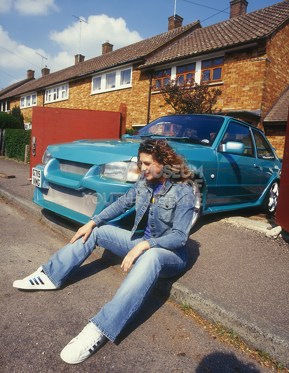 A girl next to her customised Ford Escort car, UK, 2000's