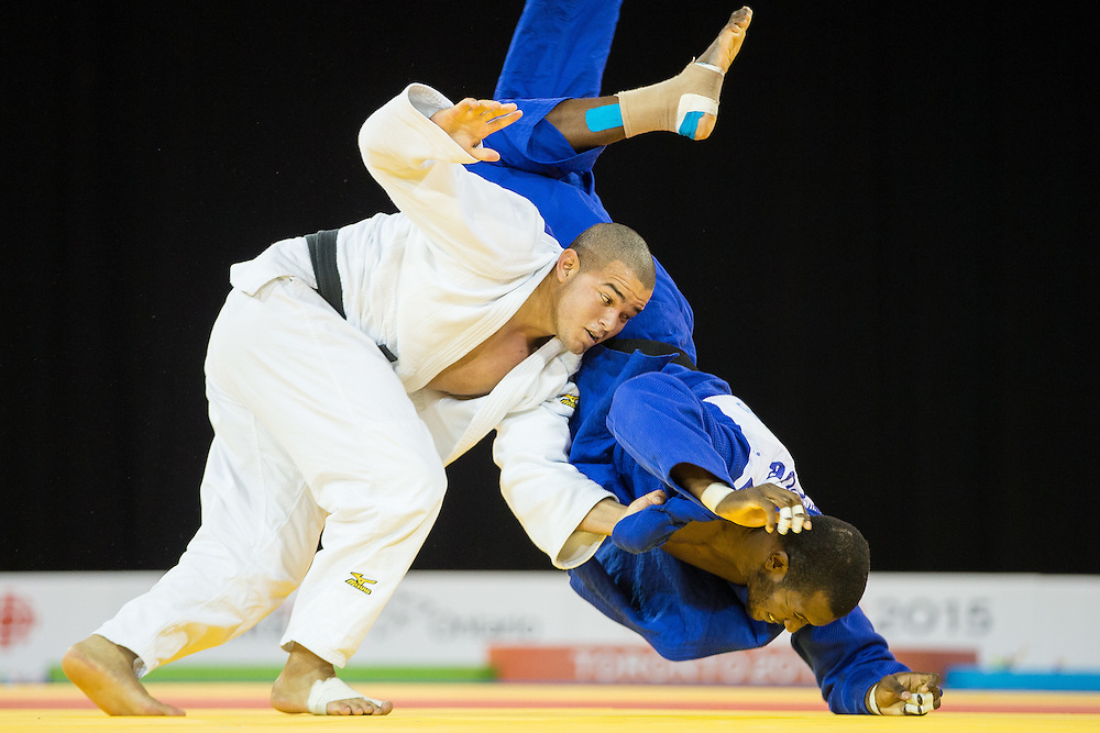 Antony Pena (L) of Venezuela throws  Jose Armenteros of Cuba during their bronze medal contest in the mens judo -100kg class at the 2015 Pan American Games in Toronto, Canada, July 14,  2015.  AFP PHOTO/GEOFF ROBINS