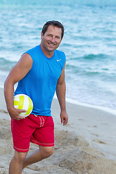 middle aged man holding a volleyball at the beach in Fort lauderdale, FL