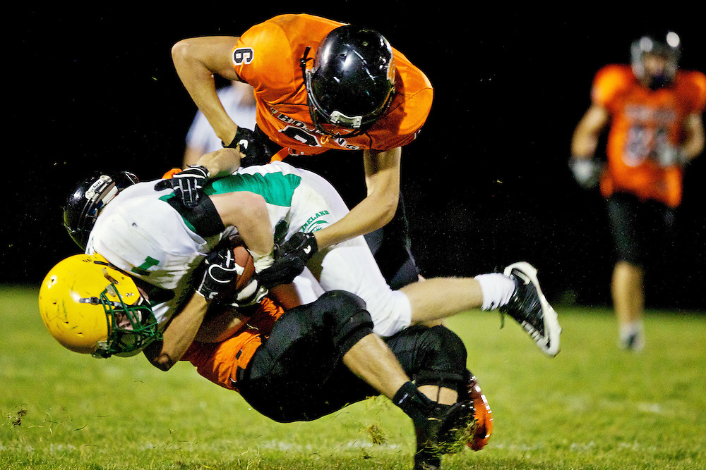 Post Falls High's Johnny Haskew, top, falls on top of Troy Carr from Lakeland as his Post Falls teammate Tyler Morris drags him down to the turf during the second half.