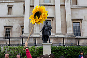 Beneath the statue of King James II (as Roman Emperor), a tour guide leader carries a sunflower for his group to follow, passing the National Portrait Gallery in Trafalgar Square on 2nd May 2019, in London, England.