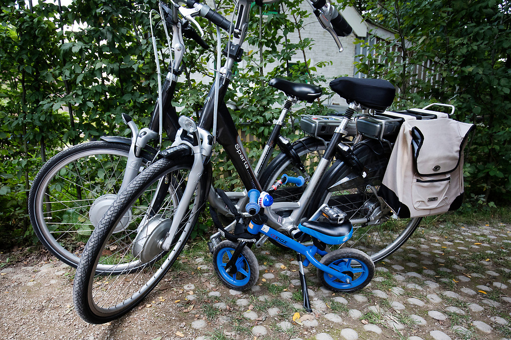 In Austerlitz staat een loopfiets vastgemaakt aan twee elektrische fietsen bij een cafe.<br /> <br /> In Austerlitz a walking bike is locked to two e-bikes near a cafe.