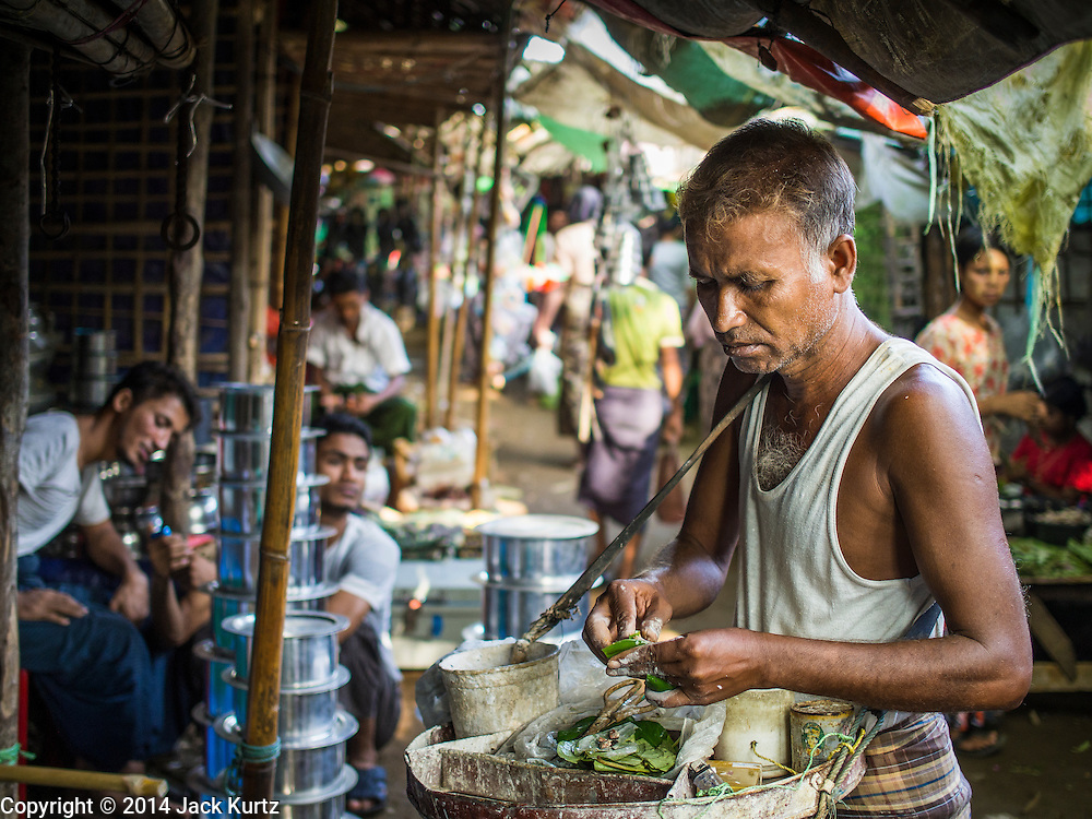 09 NOVEMBER 2014 - SITTWE, RAKHINE, MYANMAR: A Rohingya Muslim betel vendor walks shop to shop in a market in a Rohingya Muslim IDP camp near Sittwe. After sectarian violence devastated Rohingya communities and left hundreds of Rohingya dead in 2012, the government of Myanmar forced more than 140,000 Rohingya Muslims who used to live in and around Sittwe, Myanmar, into squalid Internal Displaced Persons camps. The government says the Rohingya are not Burmese citizens, that they are illegal immigrants from Bangladesh. The Bangladesh government says the Rohingya are Burmese and the Rohingya insist that they have lived in Burma for generations. The camps are about 20 minutes from Sittwe but the Rohingya who live in the camps are not allowed to leave without government permission. They are not allowed to work outside the camps, they are not allowed to go to Sittwe to use the hospital, go to school or do business. The camps have no electricity. Water is delivered through community wells. There are small schools funded by NOGs in the camps and a few private clinics but medical care is costly and not reliable.  PHOTO BY JACK KURTZ