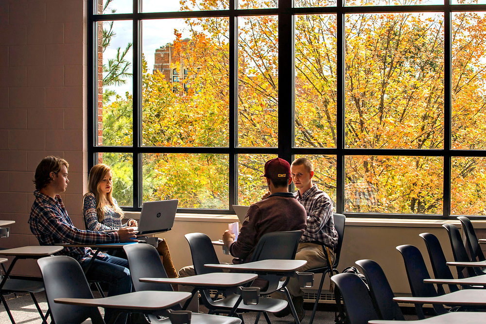 Sustainability- Many new windows have replaced older ones in Grawn Hall this past summer. The newer windows are larger and more energy efficient. Students work on a group project in between classes in an empty third floor classroom facing south towards Warriner Hall.   Central Michigan University photos by Steve Jessmore