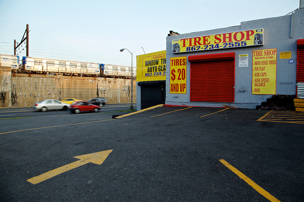 Tires in motion eventually need service. Cars pass the elevated PATH line alongside the McCarter Highway in Newark.