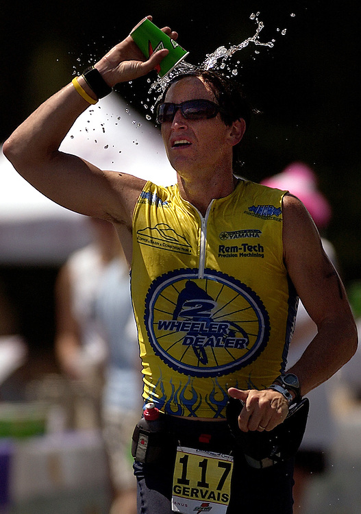 JEROME A. POLLOS/Press..Greg Gervais, of Post Falls, splashes water on his head to cool down during the marathon-leg of the Ironman.