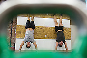 Manny Song, left, and Juan Carlos Miranda perform a handstand for two minutes during a CrossFit program at ThirdSpace Fitness in San Jose, California, on July 6, 2015. (Stan Olszewski/SOSKIphoto for Content Magazine)