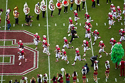 October 23, 2010; Stanford, CA, USA;  Stanford Cardinal head coach Jim Harbaugh (center) leads his team onto the field before the game against the Washington State Cougars at Stanford Stadium.