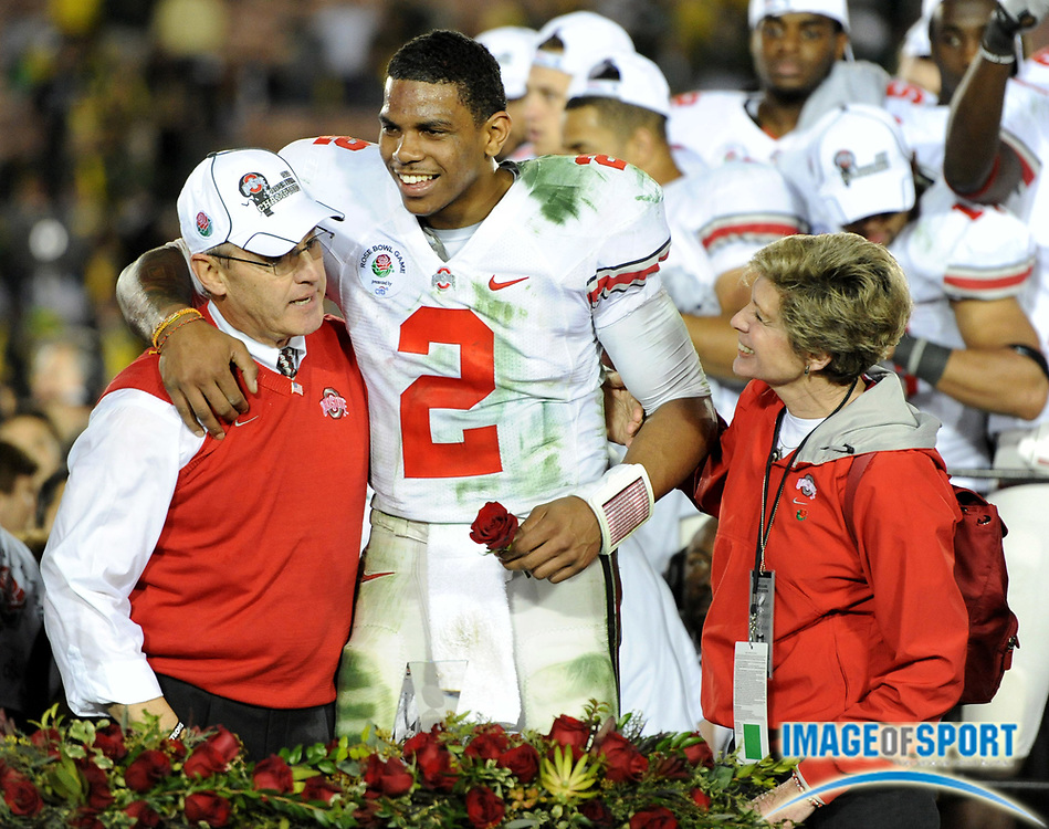 Jan 1, 2010; Pasadena, CA, USA; Ohio State Buckeyes quarterback Terrelle Pryor (2), center, is embraced by coach Jim Tressel (left) and Ellen Tressel after the 2010 Rose Bowl against the Oregon Ducks at the Rose Bowl. Ohio State defeated Oregon 26-17.