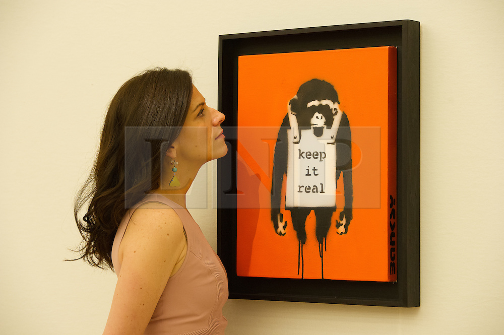 © London News Pictures. 26/06/15. London, UK. A Bonham's employee looks at Banksy's 'Keep it Real', which is part of Bonhams Contemporary Art Sale, New Bond Street, Central London. Photo credit: Laura Lean/LNP