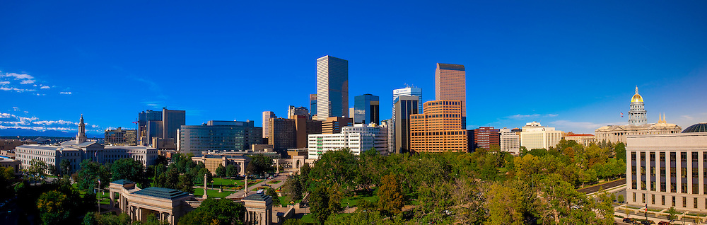 Panoramic view of Downtown skyline with City & County Bldg. on left and Colorado State Capitol Bldg. on right, and Civic Center Park in foreground, Denver, Colorado USA.