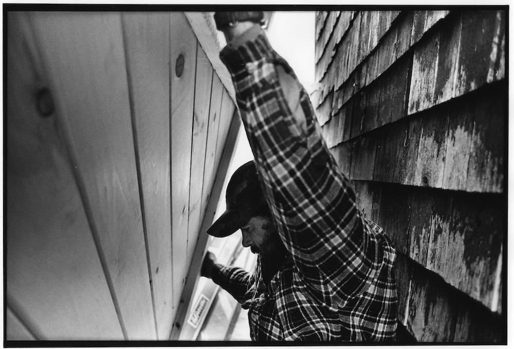 Dave Rose, barnwright, aligns a barn door on new tracks.