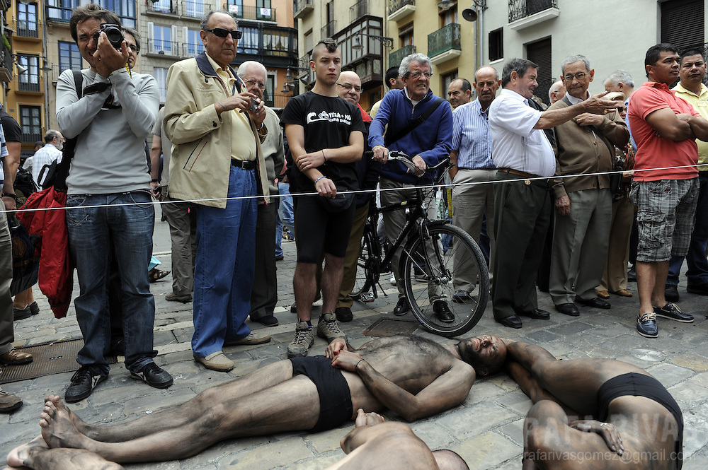 "Members of PETA and Anima Naturalis pro animal groups create ""Stop Bullfights"" words with their bodies covered in paint during a protest against bullfighting in front of the Town Hall, in the Northern Spanish city of Pamplona, on July 5, 2012, ahead of the San Fermin Festivities. PHOTO/Rafa Rivas"