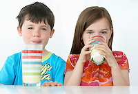 Boy and girl (5-6) sitting at table drinking milk from colourful glasses portrait