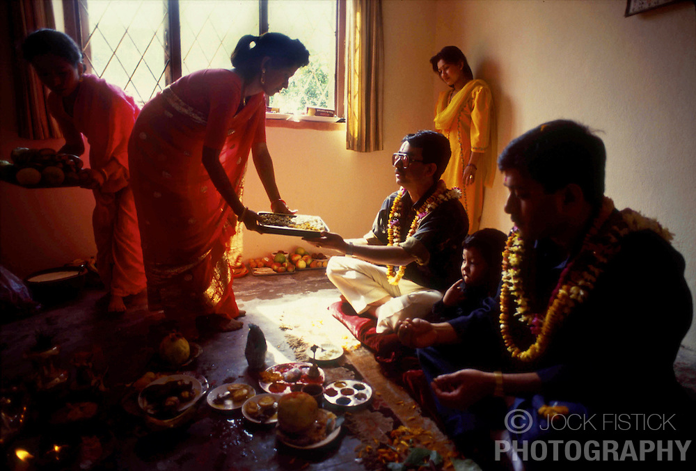KATHMANDU, NEPAL - OCTOBER 1992 -  A family clebrates the Tihar Festival also known as the  Festival of Lights. Tihar is a time when brothers and sisters pay respect to one another. The women serve an elaborate meal to the men, while the men return the gesture by giving a gift, usually money. On the fifth day, brothers and sisters pray to Yama, the god of death, that long life and prosperity be granted to their family. <br />