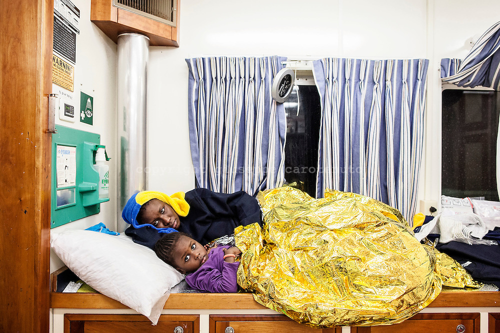 26 November 2016. Kuajia, two year old girl from Senegal, with her mother, Yasmine in the Phoenix's clinic. 146 people were rescued by MOAS (the Migrant Offshore Aid Station) on 24 November 2016 in the Mediterranean Sea. MOAS has rescued over 33,000 people between the years 2014 – 2016.