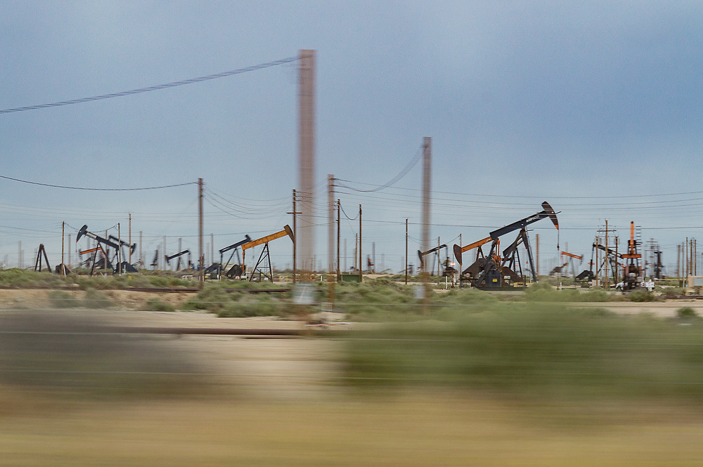 Image of many oil wells in an oil field taken from a car passing by.