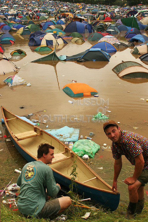 Two men with a canoe in a flooded campsite, Glastonbury 2005