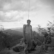 A member of the Second Infantry Division stands with a radio and antenna on a ridge top during the Korean War. These are photos of the 2nd Infantry Division in the Korean War in 1950 or 1951.