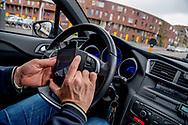 ROTTERDAM - man appt appen , whatsapp ,telefoneert achter het stuur tijdens het rijden.  nieuwe waarschuwingsborden langs de snelweg . Appen, mailen, facebooken, tweeten en sms'en in het verkeer zorgt jaarlijks voor enkele tientallen doden. Die cijfers presenteert het ministerie van Infrastructuur bij de start van een nieuwe campagne tegen het gebruik van smartphone achter het stuur of op de fiets. De campagne Aandacht op de weg loopt tot half december. Een automobilist verstuurt een bericht via WhatsApp. De politie begint een groot offensief tegen het gebruik van smartphones in de auto. Er komen intensieve controles op automobilisten die tijdens het rijden hun mobiele telefoon gebruiken voor.  copyrigt robin utrecht