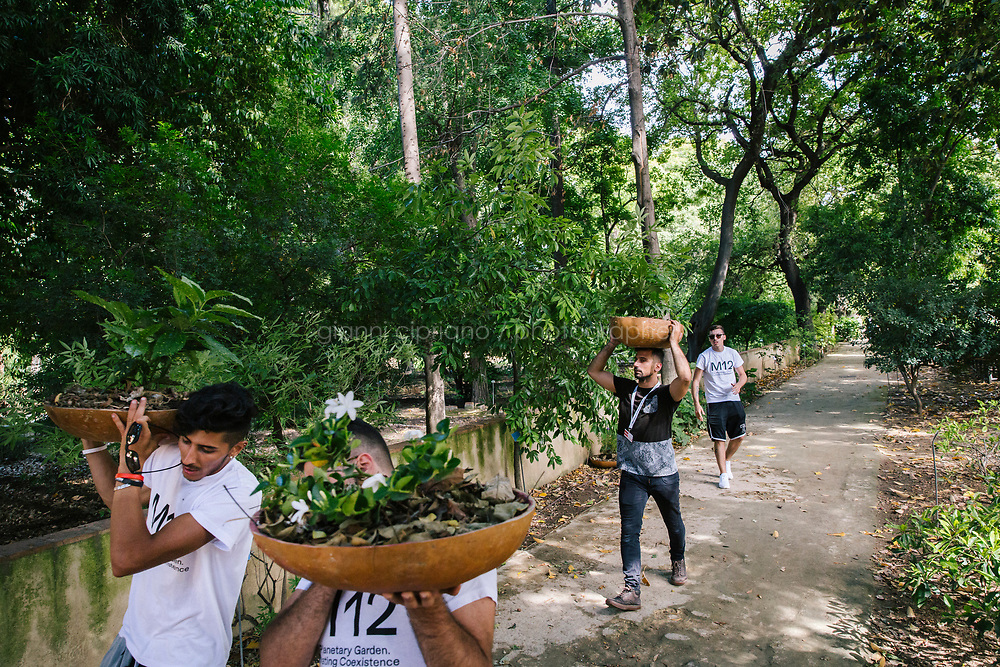 PALERMO, ITALY - 15 JUNE 2018: Staff of Manifesta 12, the European nomadic art biennal, are seen here at work in the Botanical Garden in Palermo, Italy, on June 15th 2018.<br /> <br /> Manifesta is the European Nomadic Biennial, held in a different host city every two years. It is a major international art event, attracting visitors from all over the world. Manifesta was founded in Amsterdam in the early 1990s as a European biennial of contemporary art striving to enhance artistic and cultural exchanges after the end of Cold War. In the next decade, Manifesta will focus on evolving from an art exhibition into an interdisciplinary platform for social change, introducing holistic urban research and legacy-oriented programming as the core of its model.<br /> Manifesta is still run by its original founder, Dutch historian Hedwig Fijen, and managed by a permanent team of international specialists.<br /> <br /> The City of Palermo was important for Manifesta&rsquo;s selection board for its representation of two important themes that identify contemporary Europe: migration and climate change and how these issues impact our cities.