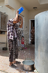 © Licensed to London News Pictures. Hamdaniyah, Iraq. 26/07/2014. Christian refugee Ra'id Samir Kamal (45), formerly a driver in Mosul, empties a container of water over his head after Kurdish Zeravani soldiers distributed fresh supplies of drinking water to refugee families living in partially built houses in Hamdaniyah, Iraq. Samir left Mosul on Friday the 18th of July when Islamic State fighters issued an ultimatum to the city's Christian community. When the family left they were forced to pay a tax for their car, their son (19) was threatened at knifepoint to ensure they handed over all of their possessions including family photographs.<br /> <br /> <br /> Having taken over Mosul Iraq's second largest city in June 2014, fighter of the Islamic State (formerly known as ISIS) have systematically expelled the cities Christian population. Despite having been present in the city for more than 1600 years, Christians in the city were given just days to either convert to Islam, pay a tax for being Christian or leave; many of those that left were also robbed at gunpoint as they passed through Islamic State checkpoints.. Photo credit : Matt Cetti-Roberts/LNP