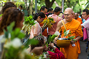 "12 JULY 2014 - PHRA PHUTTHABAT, SARABURI, THAILAND: People present monks with flowers during the Tak Bat Dok Mai at Wat Phra Phutthabat in Saraburi province of Thailand. Wat Phra Phutthabat is famous for the way it marks the beginning of Vassa, the three-month annual retreat observed by Theravada monks and nuns. The temple is highly revered in Thailand because it houses a footstep of the Buddha. On the first day of Vassa (or Buddhist Lent) people come to the temple to ""make merit"" and present the monks there with dancing lady ginger flowers, which only bloom in the weeks leading up Vassa. They also present monks with candles and wash their feet. During Vassa, monks and nuns remain inside monasteries and temple grounds, devoting their time to intensive meditation and study. Laypeople support the monks by bringing food, candles and other offerings to temples. Laypeople also often observe Vassa by giving up something, such as smoking or eating meat. For this reason, westerners sometimes call Vassa ""Buddhist Lent.""    PHOTO BY JACK KURTZ"