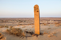 A stone marker on a sandy hill above a camp which is part of a tourist camel trek in the Thar desert of Rajasthan, India.