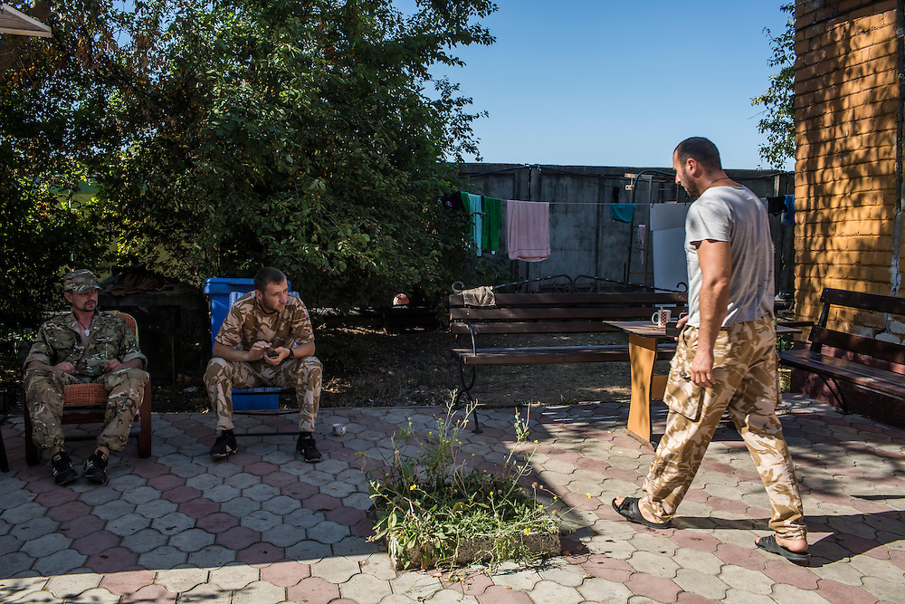 MELEKYNE, UKRAINE - AUGUST 30, 2015: Fighters from the Donbass Battalion, a pro-Ukraine militia that has been integrated into the National Guard, relax at their base in Melekyne, Ukraine. Many of the formerly autonomous battalions have recently been pulled back from the front line and replaced by regular Ukrainian soldiers, which has frustrated some of the fighters, who consider themselves battle-tested and eager to continue the fight. CREDIT: Brendan Hoffman for The New York Times