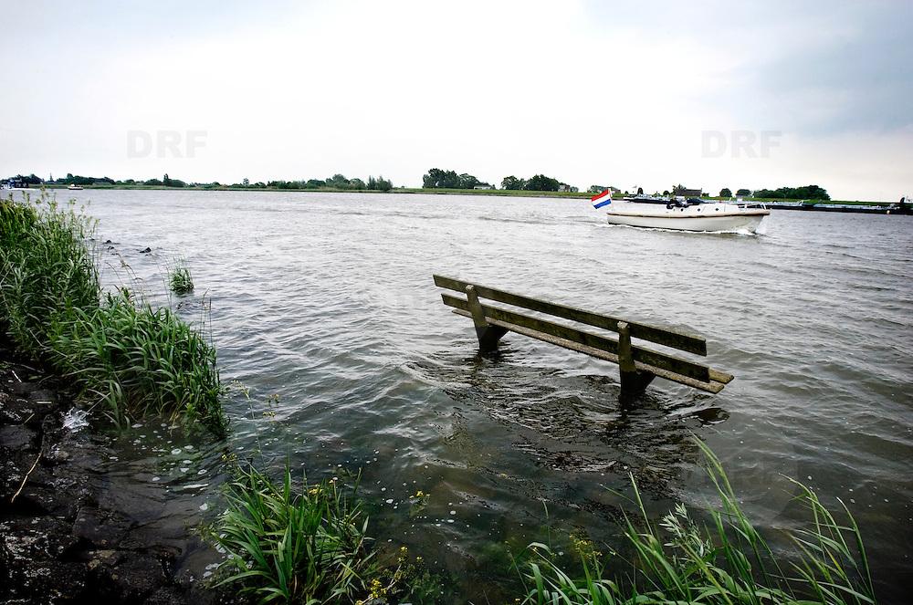 Nederland Lekkerkerk 27 mei 2007 20070527.Ondergestroomd bankje aan waterkant rivier door hoge vloed..Serie tbv Schieland en de Krimpenerwaard, deze zorgt als waterschap voor droge voeten en schoon water in een bepaald gebied. Het beheersgebied van Schieland en de Krimpenerwaard strekt zich uit tussen Rotterdam, Schoonhoven en Zoetermeer. Binnen dit gebied zorgt Schieland en de Krimpenerwaard voor de kwaliteit van het oppervlaktewater, het waterpeil en de waterkeringen. Daarnaast beheert Schieland en de Krimpenerwaard een aantal wegen in de Krimpenerwaard...Foto David Rozing