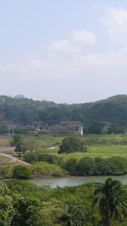 Vista desde el Canal de Panamá,Miraflores..El Canal de Panamá mide 80 Kilómetros de largo.Su cauce discurre entre el Atlántico y el Pacifico. El Canal esta conformado por varios elementos: el lago Gatún;el Corte Culebra; y las esclusas(Miraflores y Pedro Miguel en el Pacifico; y Gatún en el Atlántico)..El canal utiliza un sistema de esclusas:compartimientos con puertas de entrada y salida. Las esclusas funcionan como elevadores de agua:suben la nave desde el nivel del mar( ya sea pacífico o del Atlántico) hacia el nivel del Lago Gatún (26 metros sobre el nivel del mar) así los buques navegan a tráves del cauce del Canal en la Cordillera Central de Panamá.