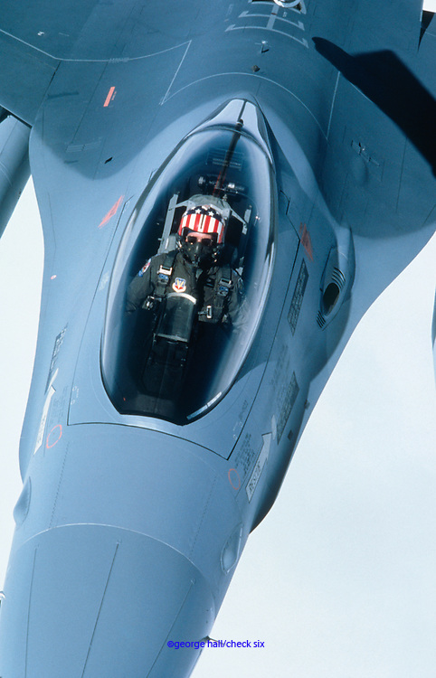 Looking down on F-16 pilot in cockpit with Stars and Stripes helmet