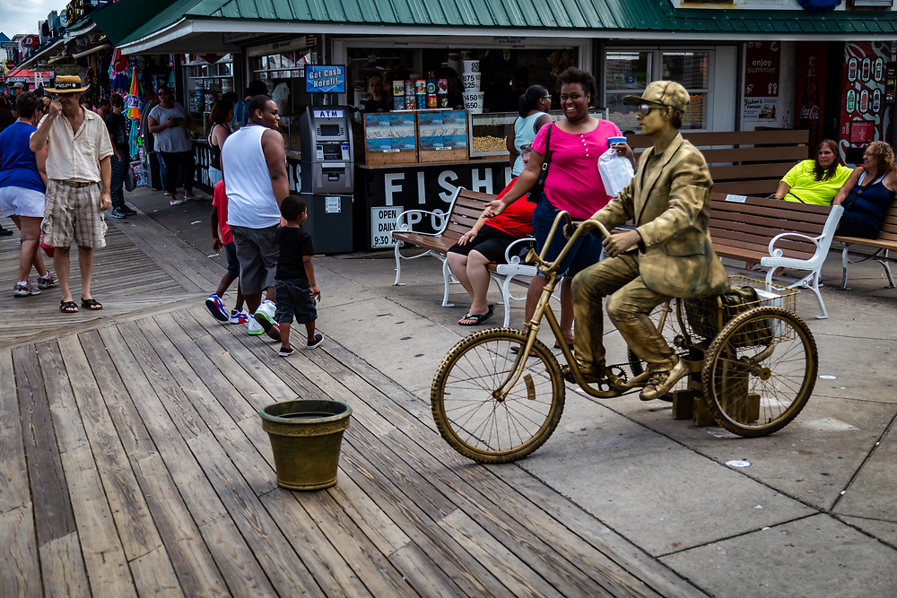 Ocean City, MD - July 10, 2016: A performance artist in gold portrays a statue man with a bike on the Ocean City boardwalk, and moves when money is dropped in a bucket.