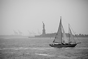 A sailboat passes in front of Liberty Island. Industrial cranes can be seen in the background.<br />