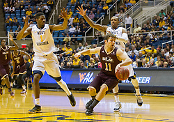 Dec 13, 2015; Morgantown, WV, USA; Louisiana Monroe Warhawks guard Nick Coppola (11) dribbles away from West Virginia Mountaineers forward Jonathan Holton (1) and guard Jevon Carter (2) during the first half at WVU Coliseum. Mandatory Credit: Ben Queen-USA TODAY Sports