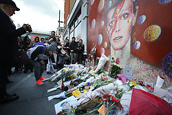 © Licensed to London News Pictures. 11/01/2016. London, UK. A fan places flowers with other tributes below a mural of David Bowie in Brixton. The Death of David Bowie, who was born in Brixton, has been announced today.  Photo credit: Peter Macdiarmid/LNP