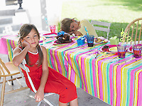 Girl and boy (7-9) at table after birthday party boy sleeping