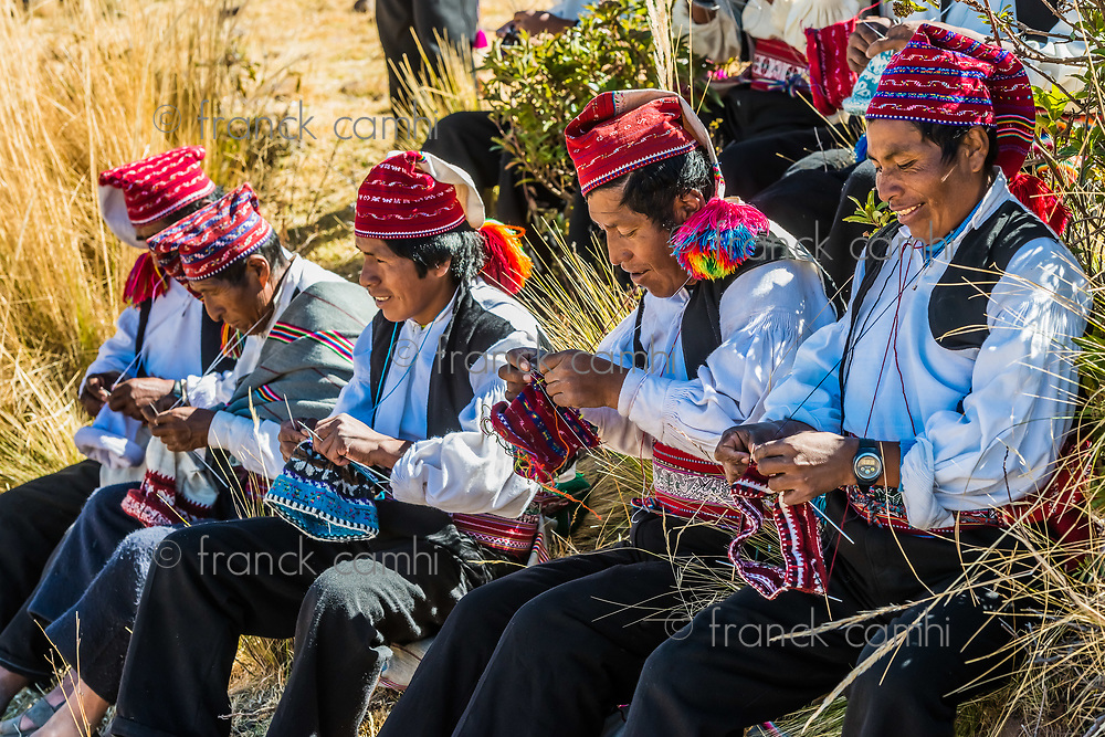 Puno, Peru - July 25, 2013: men weaving in the peruvian Andes at Taquile Island on Puno Peru at july 25th, 2013.