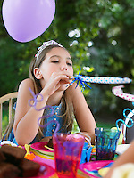 Young girl (10-12) blowing party puffer at birthday party