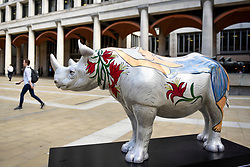 **CAPTION CORRECTION - Rhino statues are 750mm tall, not 750cm tall, as stated in previous captions**<br /> © Licensed to London News Pictures. 20/08/2018. LONDON, UK. An office worker passes by 'Marjorie', a rhino painted by Eileen Cooper, in Paternoster Square.  At 750mm tall and weighing 300 kg, each rhino has been specially embellished by an internationally renowned artist.  21 rhinos are in place at a popular location in central London, forming the Tusk Rhino Trail, until World Rhino Day on 22 September to raise awareness of the severe threat of poaching to the species' survival.  They will then be auctioned by Christie's on 9 October to raise funds for the Tusk animal conservation charity.  Photo credit: Stephen Chung/LNP