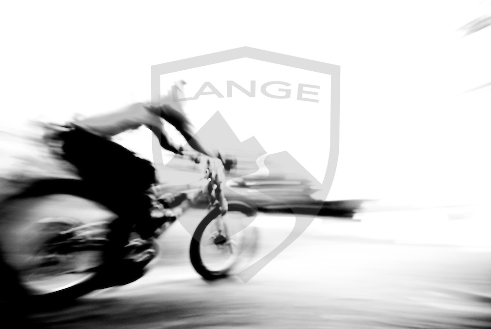 a mountain biker speeds by in black and white creating abstract impressions of speed and motion.  taken in the sandia mountains downhill mountain bike trails, near albuquerque, new mexico.