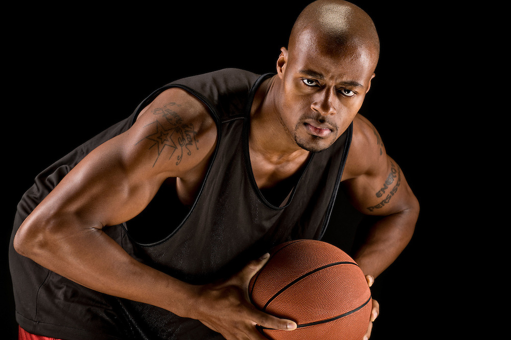Basketball player looking at camera with ball.