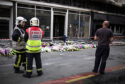 © Licensed to London News Pictures . FILE PICTURE DATED 15/07/2013 . Oldham Street , Manchester , UK .  Firemen stand by flowers and tributes left at the scene on Oldham Street following a fire at Paul 's Hair World on 13th July which claimed the life of fireman Stephen Hunt . Photo credit : Joel Goodman/LNP