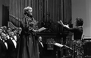 An operatic diva sings open-mouthed accompanied by a Welsh male voice choir during a rehearsal at St Paul's church, Newport