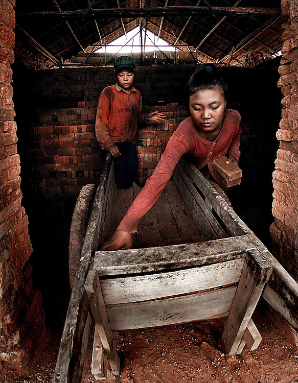 Girls loading a trolley with bricks from a kiln in Sainyabuli province, Laos.