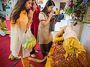 17 AUGUST 2014 - BANGKOK, THAILAND:   Women pray at the crib that represents the crib of Krishna during Krishna Janmashtami observances at the Vishnu temple in Bangkok. Krishna Janmashtami is the annual celebration of the birth of the Hindu deity Krishna, the eighth avatar of the Hindu god Vishnu. It is celebrated by Hindus in Thailand. There are about 53,000 Hindus in Thailand, most originally from India, but many Hindu deities are highly revered by Thai Buddhists and Hindu holy days are observed by many Thai Buddhists.    PHOTO BY JACK KURTZ